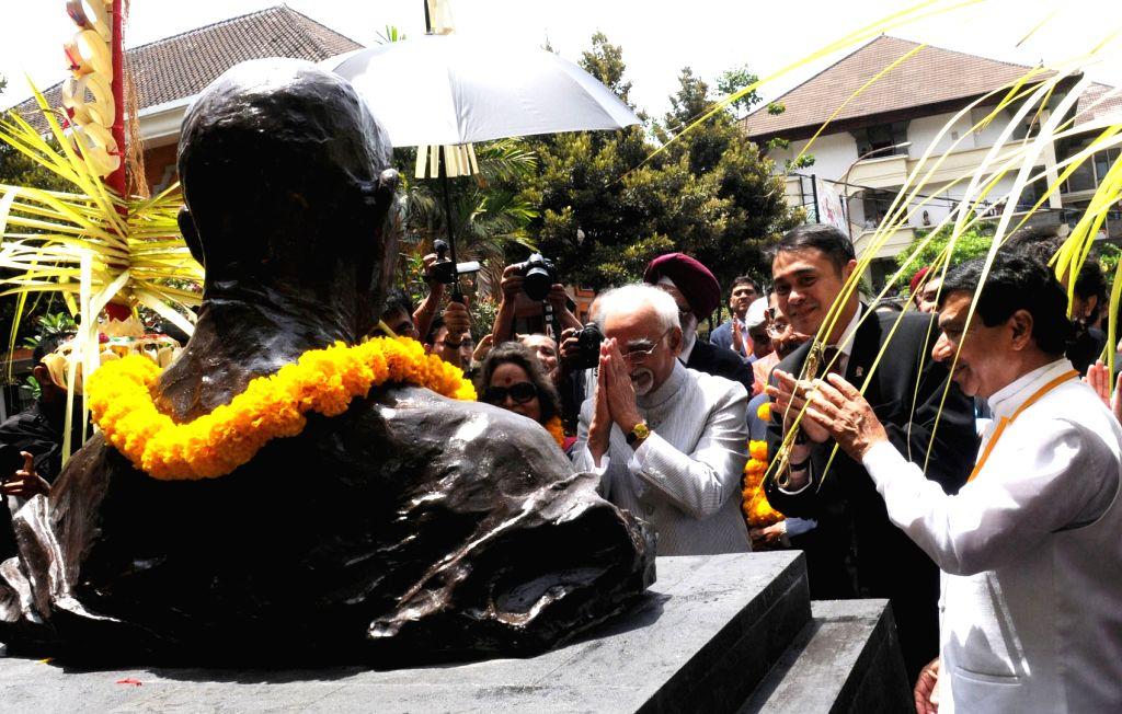 :Bali: Vice President Mohd. Hamid Ansari pays homage after unveiling the bust of Mahatma Gandhi, at Udayana University, in Bali, Indonesia, on Nov 4, 2015. (Photo: IANS/PIB).