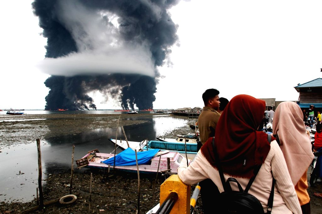 BALIKPAPAN, March 31, 2018 - People watch the rising black smoke from a burned oil spill at the waters in Balikpapan, Indonesia, March 31, 2018. A cargo ship caught fire in waters off East Kalimantan ...