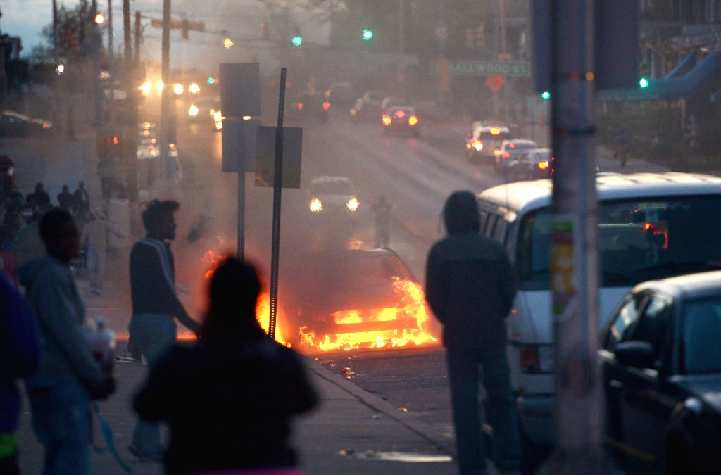 A car burns in Baltimore, Maryland, the United States, April 27, 2015. Maryland governor Larry Hogan Monday evening declared a state of emergency and activated ...