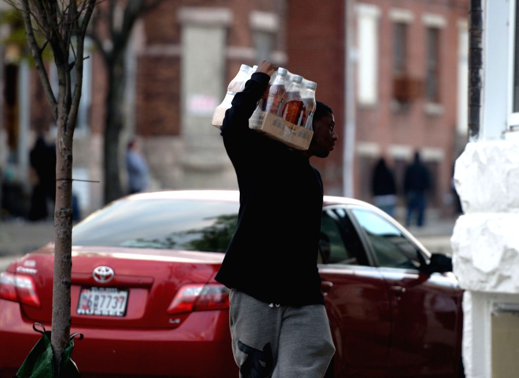 A man carries goods looted from a store in Baltimore, Maryland, the United States, April 27, 2015. Maryland governor Larry Hogan Monday evening declared a state ...