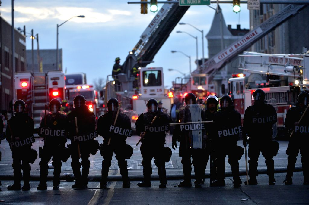 Policemen guard near a CVS pharmacy store which was set ablaze in Baltimore, Maryland, the United States, April 27, 2015. Maryland governor Larry Hogan Monday ...