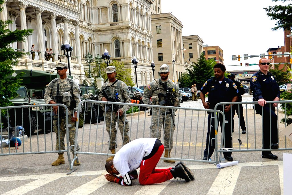 A man gets down on his knees in front of curfew zone of the City Hall in Baltimore, Maryland, the United States, May 2, 2015. Thousands of people in Baltimore, the ...
