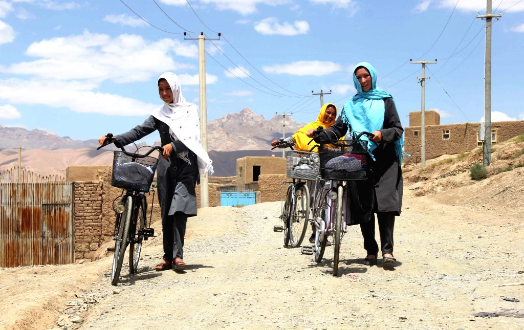 BAMYAN, July 18, 2016 - Afghan girls walk alongside their bicycles after a ceremony in Bamyan province, Afghanistan, July 18, 2016. Afghan Family Guidance Association (AFGA), a local non-governmental ...
