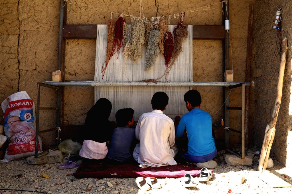 Afghan children weave carpet at a house in Bamyan province in central Afghanistan, July 21, 2014.