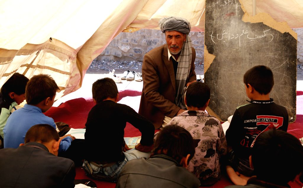 , 2014 An Afghan teacher teaches students at a class in Bamyan province in central Afghanistan on May 13, 2014.