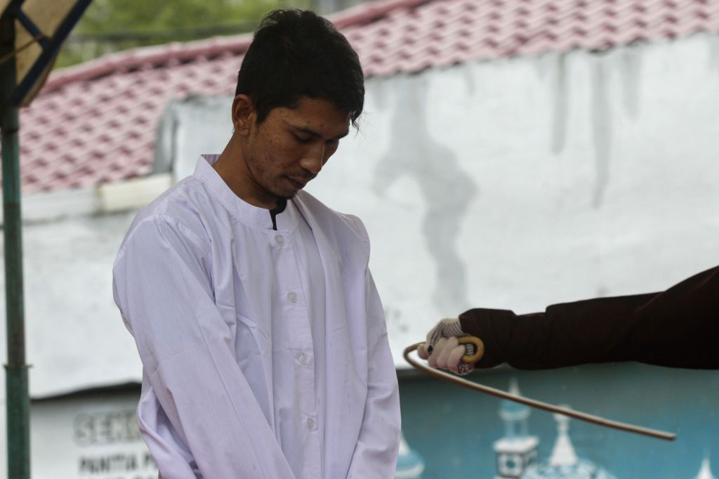 BANDA ACEH, Oct. 17, 2016 - An Acehnese man is whipped in front of the public at the Baiturrahman Grand Mosque in Banda Aceh, Indonesia, Oct. 17, 2016. Seven Acehnese couples were sentenced to be ...