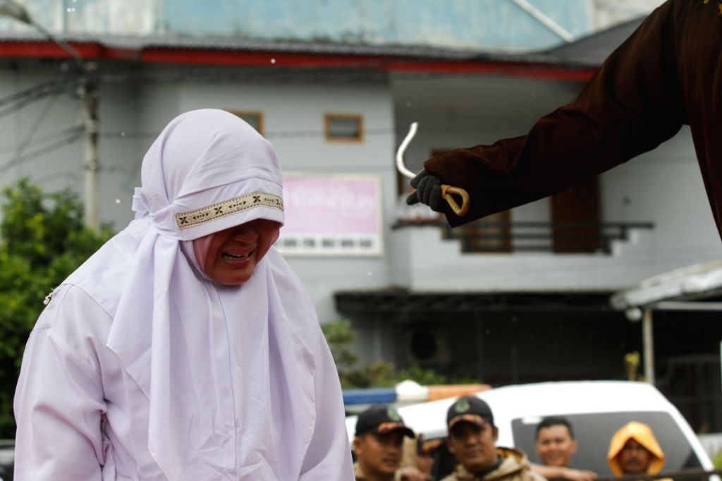 BANDA ACEH, Oct. 17, 2016 - An Acehnese woman is whipped in front of the public at the Baiturrahman Grand Mosque in Banda Aceh, Indonesia, Oct. 17, 2016. Seven Acehnese couples were sentenced to be ...