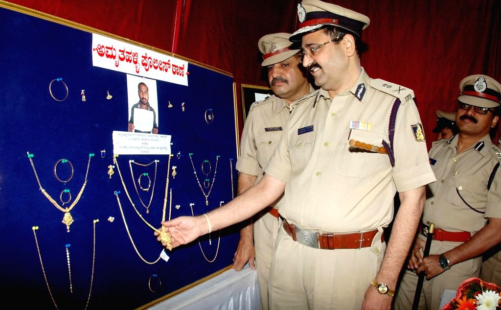 Bangalore City Police Commissioner Ragavendra Auradkar looking at jewellery which were recovered at Police commissioner Office, in Bangalore on Dec. 7, 2013.