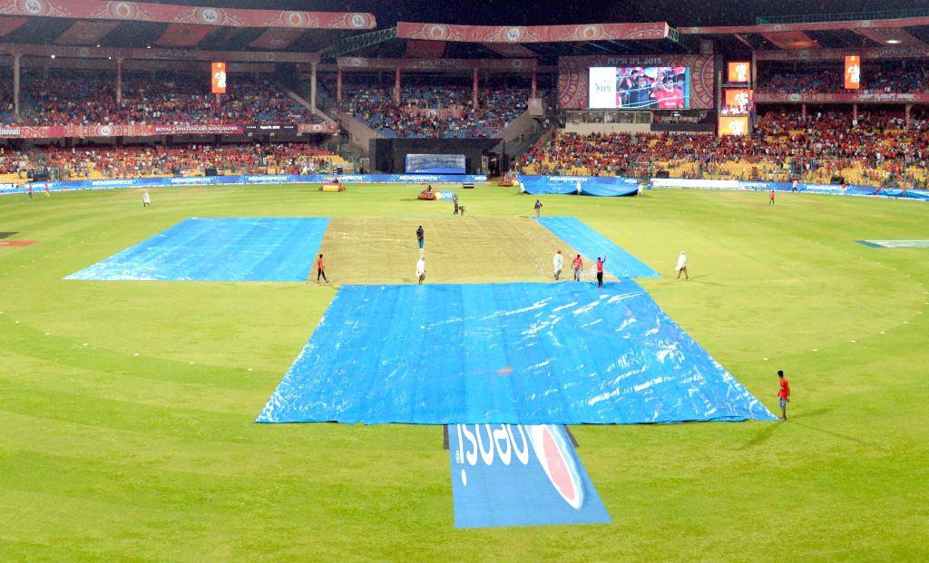 Ground staff at work as rain disrupts an IPL-2015 match between Royal Challengers Bangalore and Kolkata Knight Riders at M Chinnaswamy Stadium in Bangaluru on May 2, 2015.