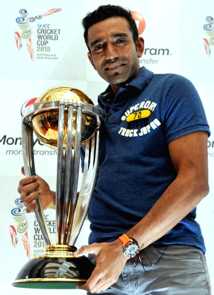 Indian cricketer Robin Uthappa unveils the ICC World Cup 2014 trophy during an ICC programme in Bangaluru on Dec 4, 2014.