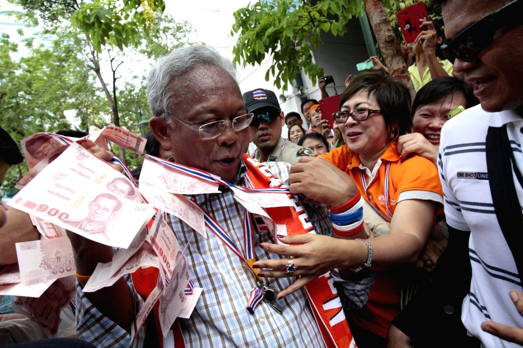 Anti-government protest leader Suthep Thaugsuban (L) greets Metropolitan Electricity Authority officials during an anti-government protest at Metropolitan ...