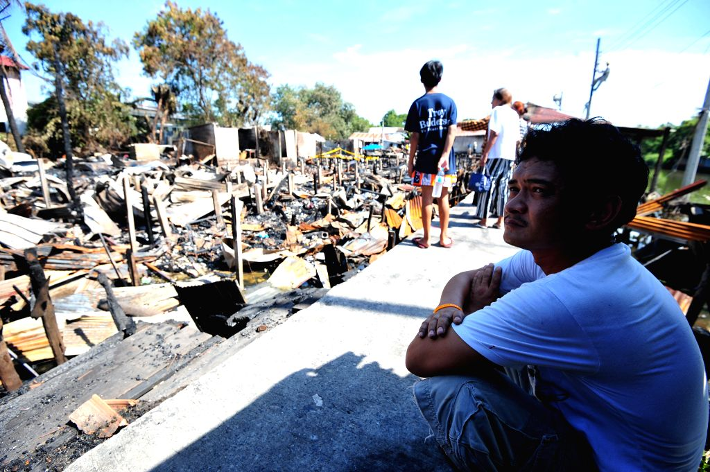 BANGKOK, Dec. 4, 2017 - A resident sits next to the ruins of a community after a fire broke out here on Sunday evening in Ladkrabang district of suburban Bangkok, Thailand, Dec. 4, 2017. No casualty ...