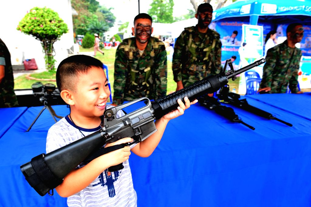A child tries on a machine gun on Children's Day at the Royal Thai Navy Academy in south Bangkok, Thailand, Jan. 10, 2015. The Thai National Children's Day is ...