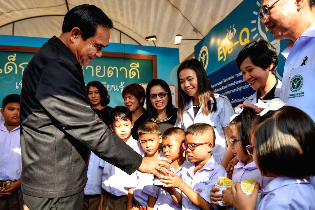 BANGKOK, Jan. 14, 2017 - Thai Prime Minister Prayuth Chan-ocha (L) gives presents to kids attending an eye health corner during a Children's Day celebration at the Sanam Suea Pa Park in Bangkok, ... - Prayuth Chan