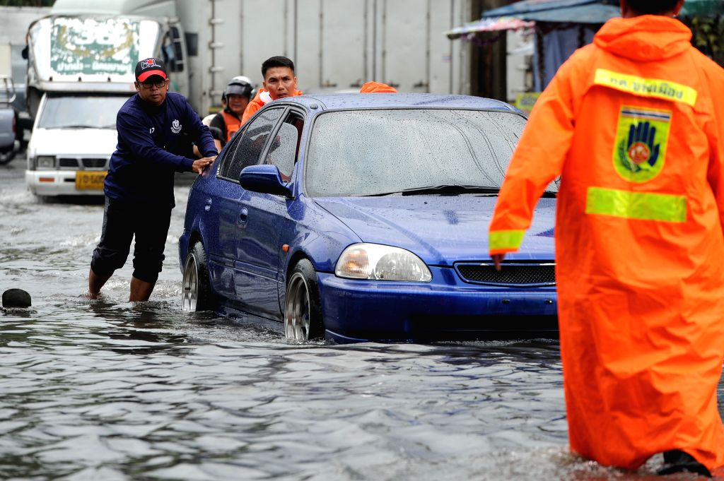 BANGKOK, Jan. 31, 2018 - People push a car that has broken down on a flooded street in Bangkok, Thailand, Jan. 31, 2018. A number of streets in Bangkok have been flooded after heavy rainfall hit the ...