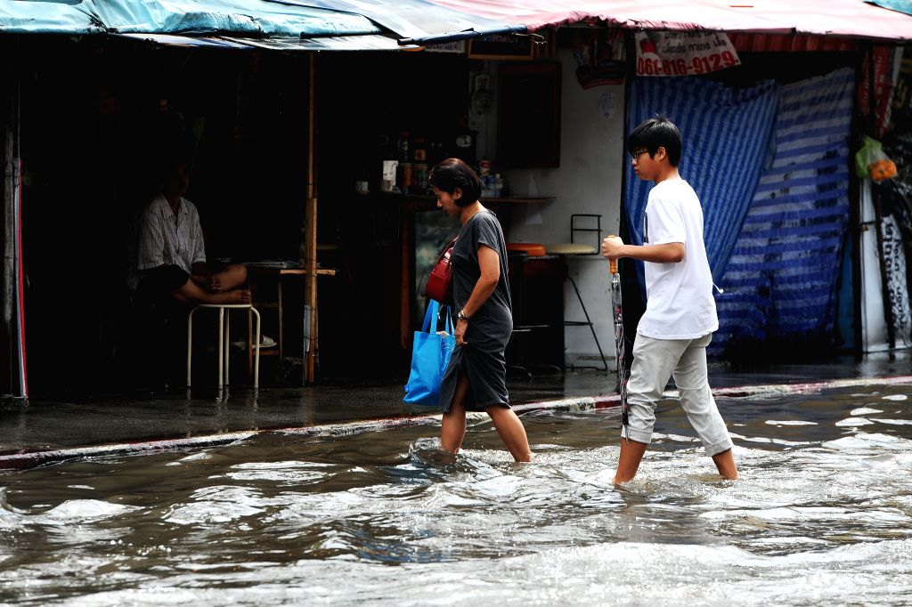 BANGKOK, Jan. 31, 2018 - Two pedestrians wade across a flooded street in Bangkok, Thailand, Jan. 31, 2018. A number of streets in Bangkok have been flooded after heavy rainfall hit the capital city ...