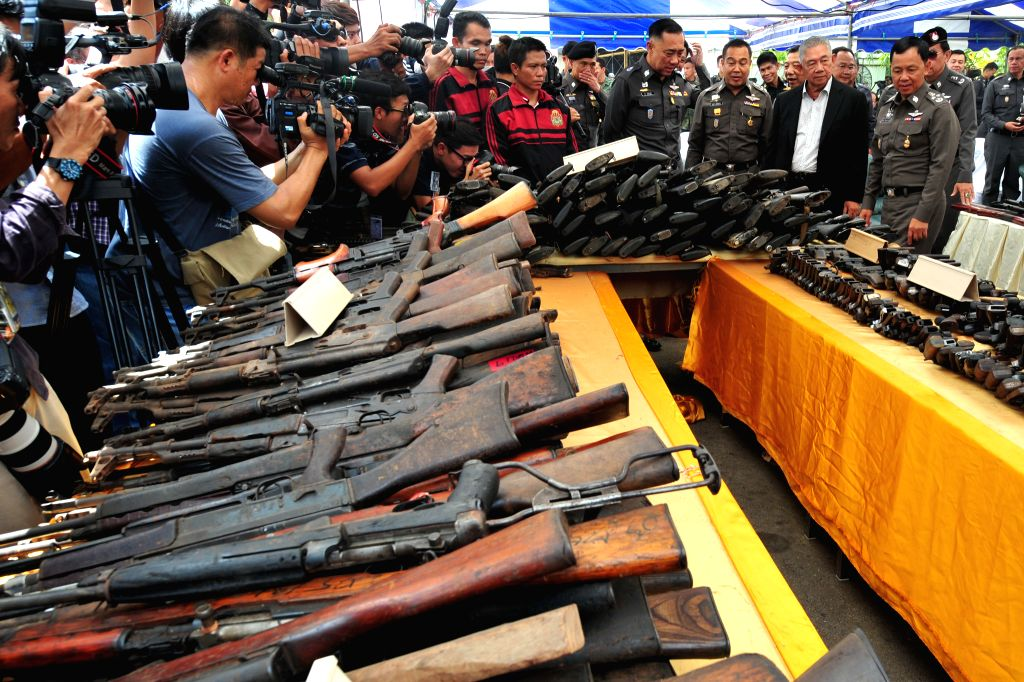 Acting National Police Chief Gen. Watcharapol Prasarnrajkit (1st R, front) looks at seized guns to be destroyed at Ironworks factory near Bangkok, Thailand, July ...