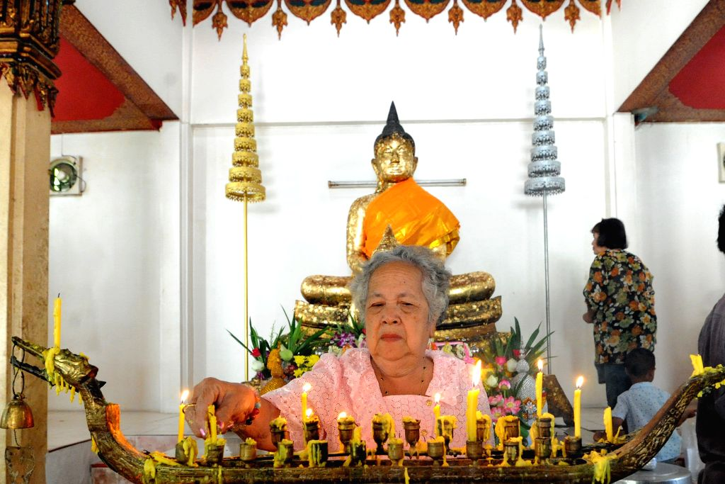 """BANGKOK, July 19, 2016 - A Thai woman lights candles at a temple in Bangkok, Thailand, July 19, 2016. Thai Buddhists across the country are ready to celebrate the Buddhist Lent Day or """"Khao ..."""