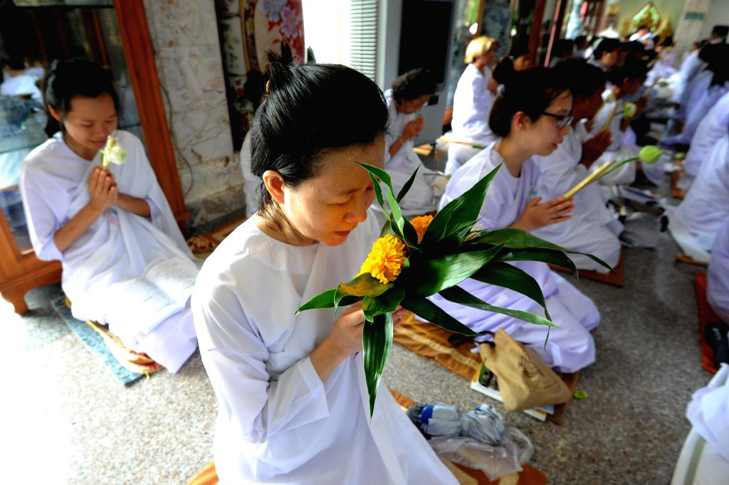 BANGKOK, July 20, 2016 - Thai people wearing white clothes listen to a monk's sermons at a temple in Bangkok, Thailand, July 20, 2016. Thai Buddhists across the country are ready to celebrate the ...