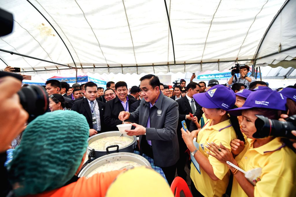 Thai Prime Minister Prayuth Chan-ocha (C) tastes a dessert after attending the International Labor Day celebration at the Sanam Luang square in Bangkok, Thailand, May ... - Prayuth Chan