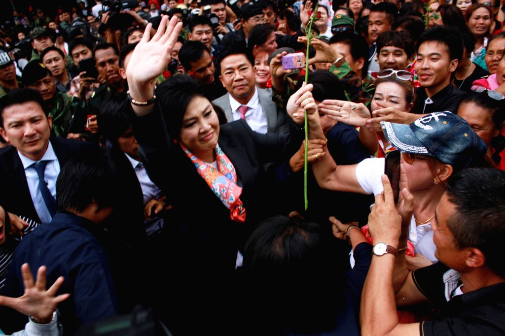 Thai caretaker Prime Minister Yingluck Shinawatra(C) greets supporters after a press conference in Bangkok, Thailand, May 7, 2014. Thailand's Constitutional Court on .