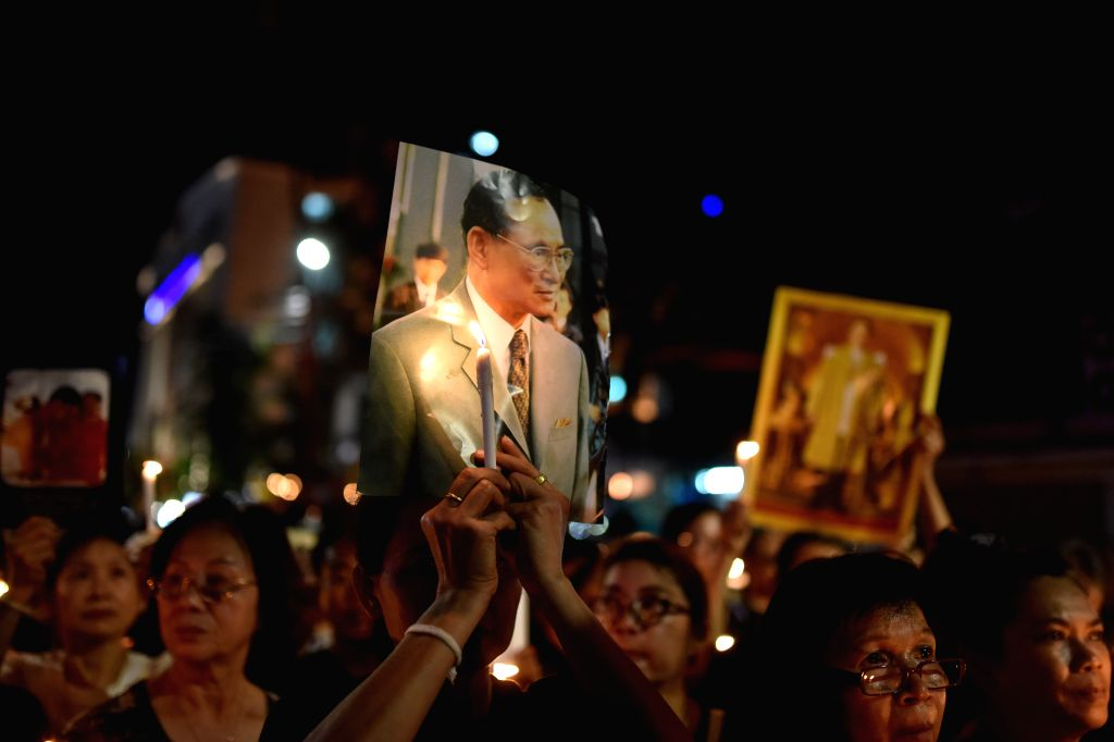 BANGKOK, Nov. 26, 2016 - Mourners hold photos of Thailand's late King Bhumibol Adulyadej with lit-up candles during a mourning event held at the Chinatown of Bangkok, Thailand, on Nov. 26, 2016. ...
