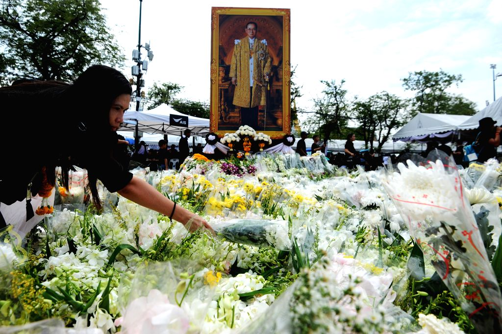 BANGKOK, Oct. 24, 2016 - A woman lays a bunch of flowers in front of a portrait of late Thai King Bhumibol Adulyadej at the Sanam Luang square in Bangkok, Thailand, Oct. 24, 2016. King Bhumibol, the ...