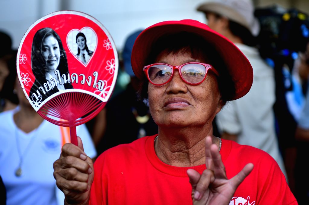 BANGKOK, Sept. 27, 2017 - A supporter holding a fan with portraits of former Thai prime minister Yingluck Shinawatra is seen at Thailand's Supreme Court in Bangkok, capital of Thailand on Sept. 27, ... - Yingluck Shinawatra