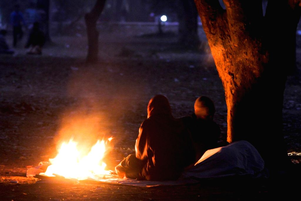 People warm themselves around a fire lit in the open in Bangladesh  on Jan 19, 2015.