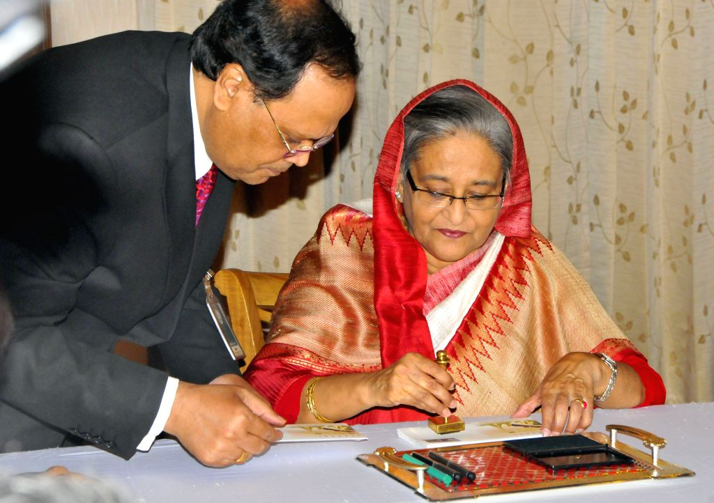 Bangladeshi Prime Minister Sheikh Hasina (R) signs to issue a commemorative stamp and envelop at prime minister residence in Dhaka, Bangladesh, Oct. 17, 2015. China ... - Sheikh Hasina