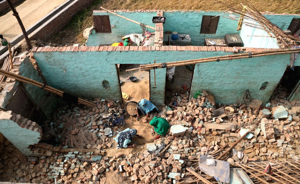 BARA, April 2, 2019 (Xinhua) -- A family works inside a house damaged by a massive storm in Purainiya village, Bara district of Nepal, April 2, 2019. At least 25 people were killed and 400 others injured when a storm devastated villages in two distri - K., P. Sharma Oli and Sunil Sharma
