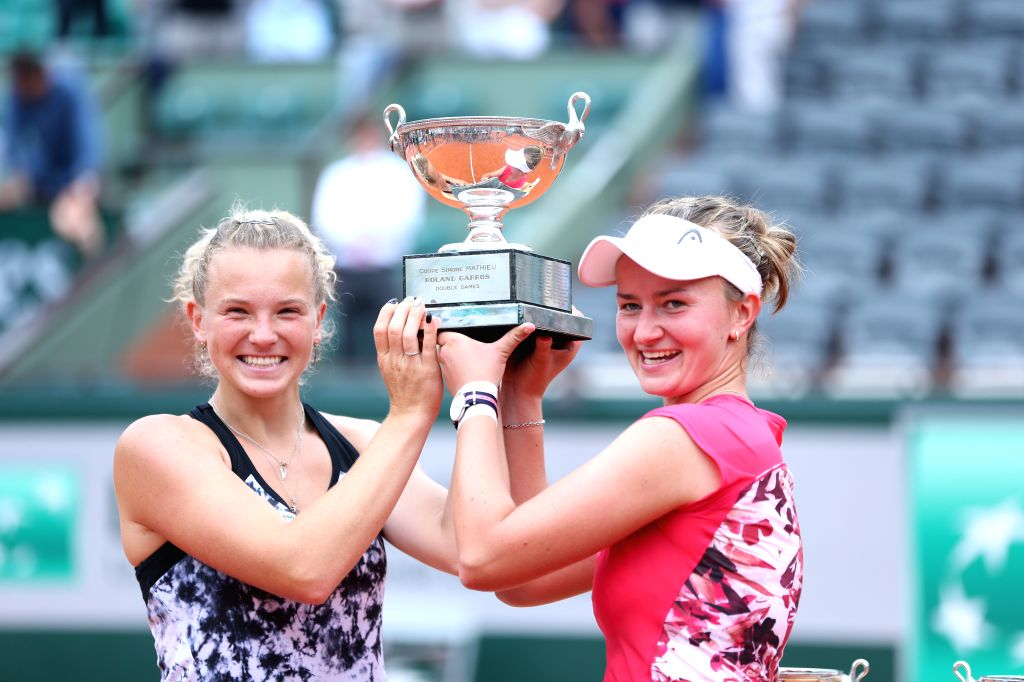 : Barbora Krejcikova (R) and Katerina Siniakova of the Czech Republic lift the trophy during the awarding ceremony for the women's doubles final at the French ...