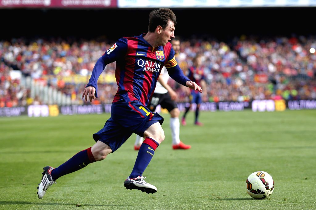Barcelona's Lionel Messi (C) breaks through during the Spanish first division football match against Valencia in Barcelona, Spain, April 18, 2015. (Xinhua/Pau ...