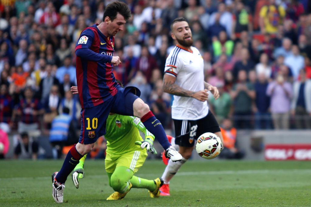 Barcelona's Lionel Messi (L) breaks through during the Spanish first division football match against Valencia in Barcelona, Spain, April 18, 2015. (Xinhua/Pau ...