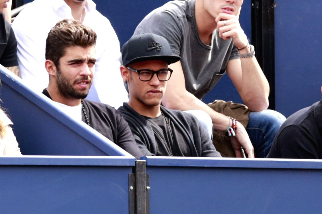 Barcelona's Brazilian forward Neymar da Silva Santos Junior (R) watches the match between Spanish players Rafael Nadal and Nicolas Almagro at the ATP Barcelona ...