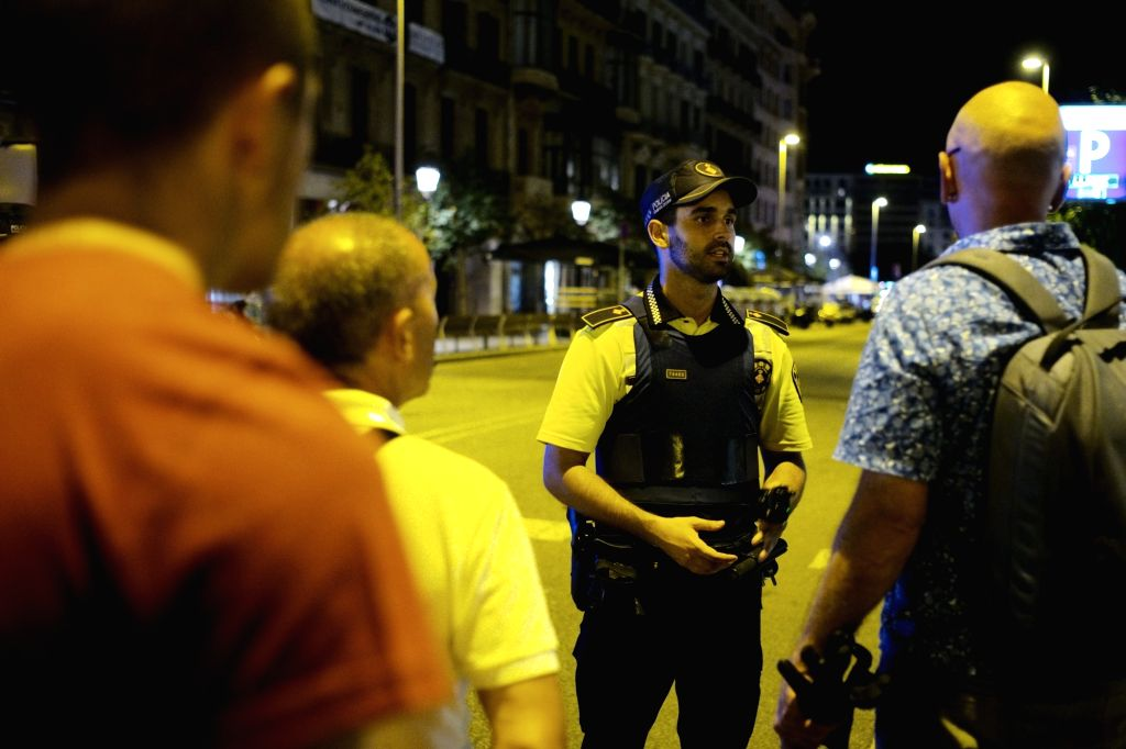 BARCELONA, Aug. 18, 2017 - A security staff talks to pedestrians following a terrorist attack in central Barcelona, Spain, on Aug. 17, 2017. Thirteen people were confirmed dead and more than 100 ...