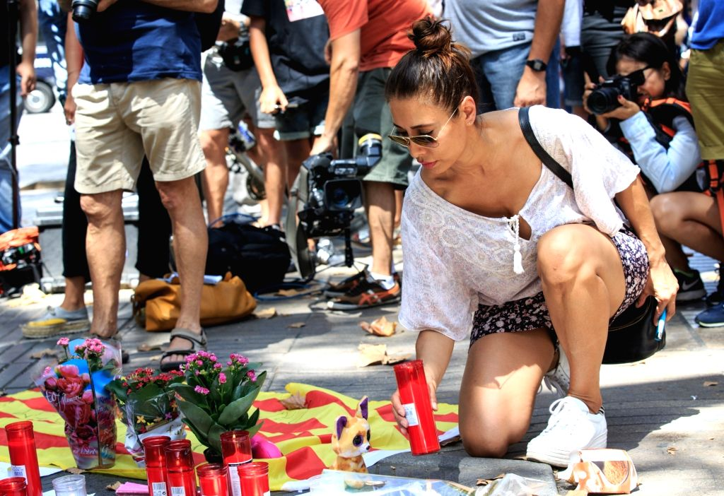 BARCELONA, Aug. 18, 2017 - A woman mourns victims of the terror attack on Las Ramblas area, Barcelona, Spain, on Aug. 18, 2017. At least 14 died in Thursday's double terror attacks in Spain, as ...