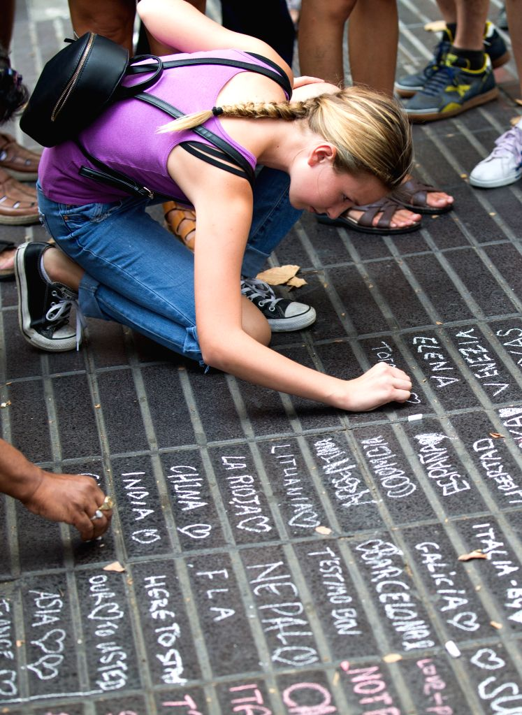 BARCELONA, Aug. 20, 2017 - A woman leaves messages with chalks to mourn for victims in the terrorist attacks on the avenue in the Las Ramblas area of Barcelona, Spain, Aug. 19, 2017. The Spanish ...