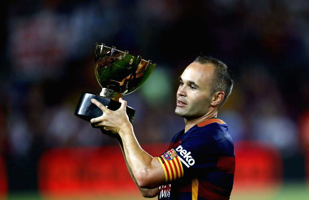 Barcelona captain Andres Iniesta holds the trophy up after defeating Roma during their Joan Gamper trophy friendly soccer match between FC Barcelona and AS Roma at Camp Nou stadium in ... - Andres Iniesta