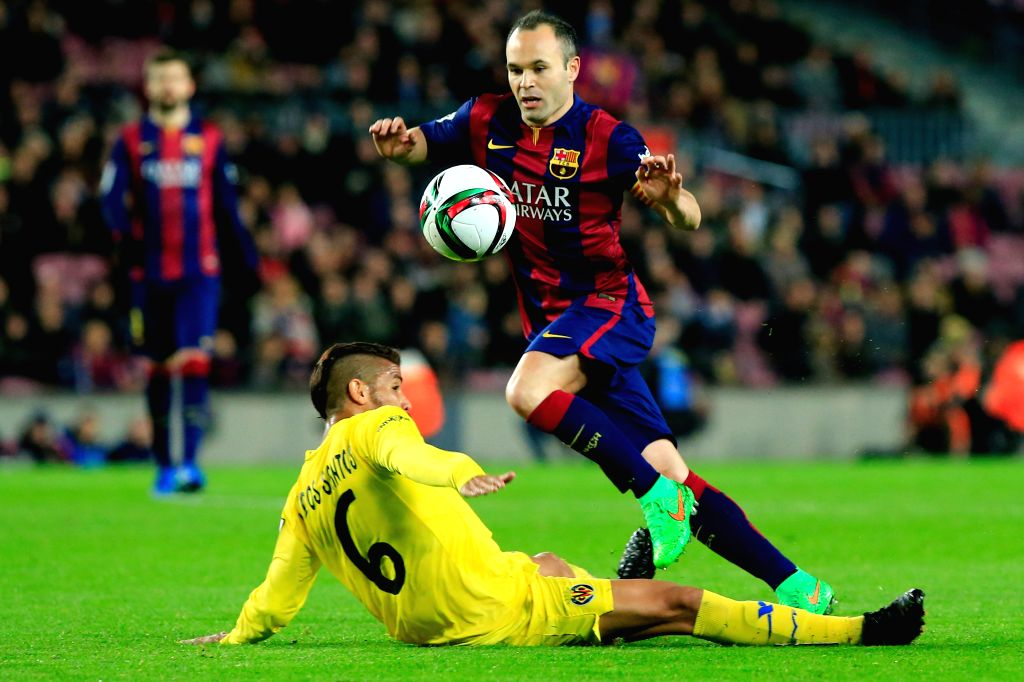 Barcelona's Andres Iniesta (R) vies with Villareal's Dos Santos during the King's Cup semifinal first leg soccer match at the Nou Camp Stadium in Barcelona, ...