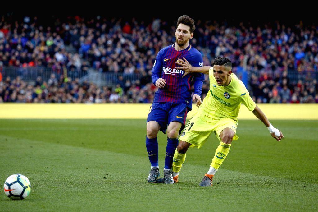 BARCELONA, Feb. 12, 2018 - Barcelona's Lionel Messi (L) vies with Getafe's Faycal Fajr during a Spainish league soccer match between Barcelona and Getafe in Barcelona, Spain, Feb. 11, 2018. The match ...