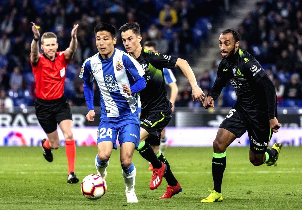 BARCELONA, Feb. 22, 2019 - Espanyol's Wu Lei (2nd L) dribbles  during a Spanish league match between Espanyol and Huesca in Barcelona, Spain, Feb.22, 2019.