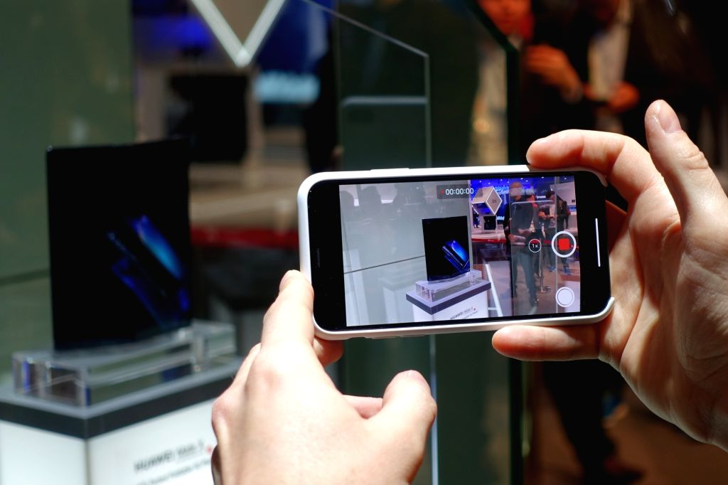 BARCELONA, Feb. 25, 2019 - A visitor takes pictures of a Huawei MATE X, a foldable 5G ready smartphone, displayed at the 2019 Mobile World Congress (MWC) in Barcelona, Spain, Feb. 25, 2019. The ...