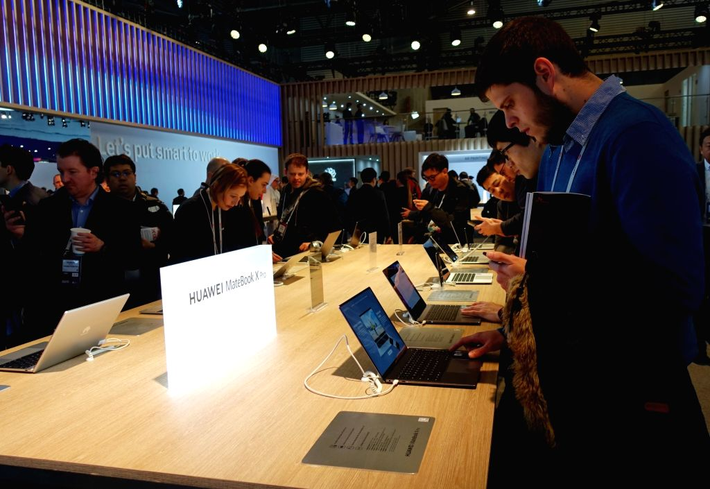 BARCELONA, Feb. 25, 2019 - Visitors try on Huawei MateBook X Pro laptops at the 2019 Mobile World Congress (MWC) in Barcelona, Spain, Feb. 25, 2019. The four-day 2019 MWC opened on Monday in ...