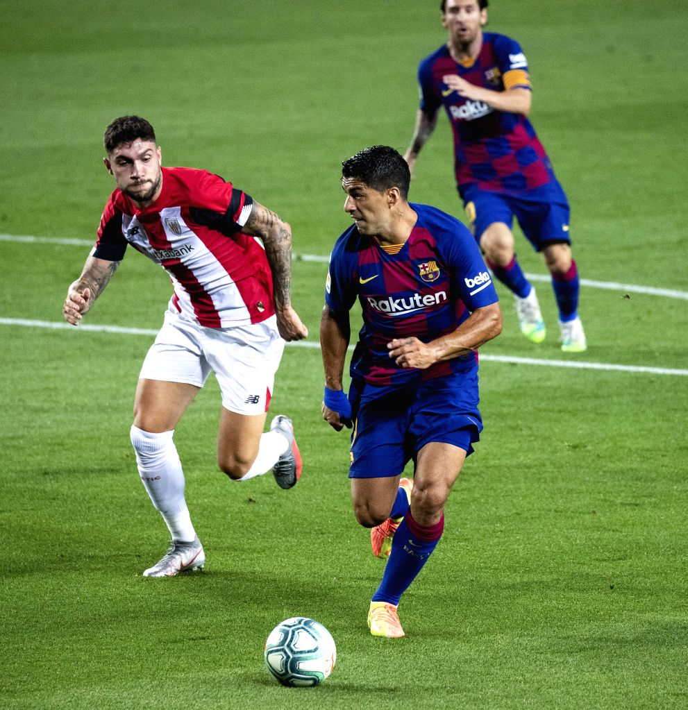 Barcelona's Luis Suarez (C) competes with Athletic Bilbao's Unai Nunez (L) during a Spanish league football match in Barcelona, Spain, June 23, 2020.