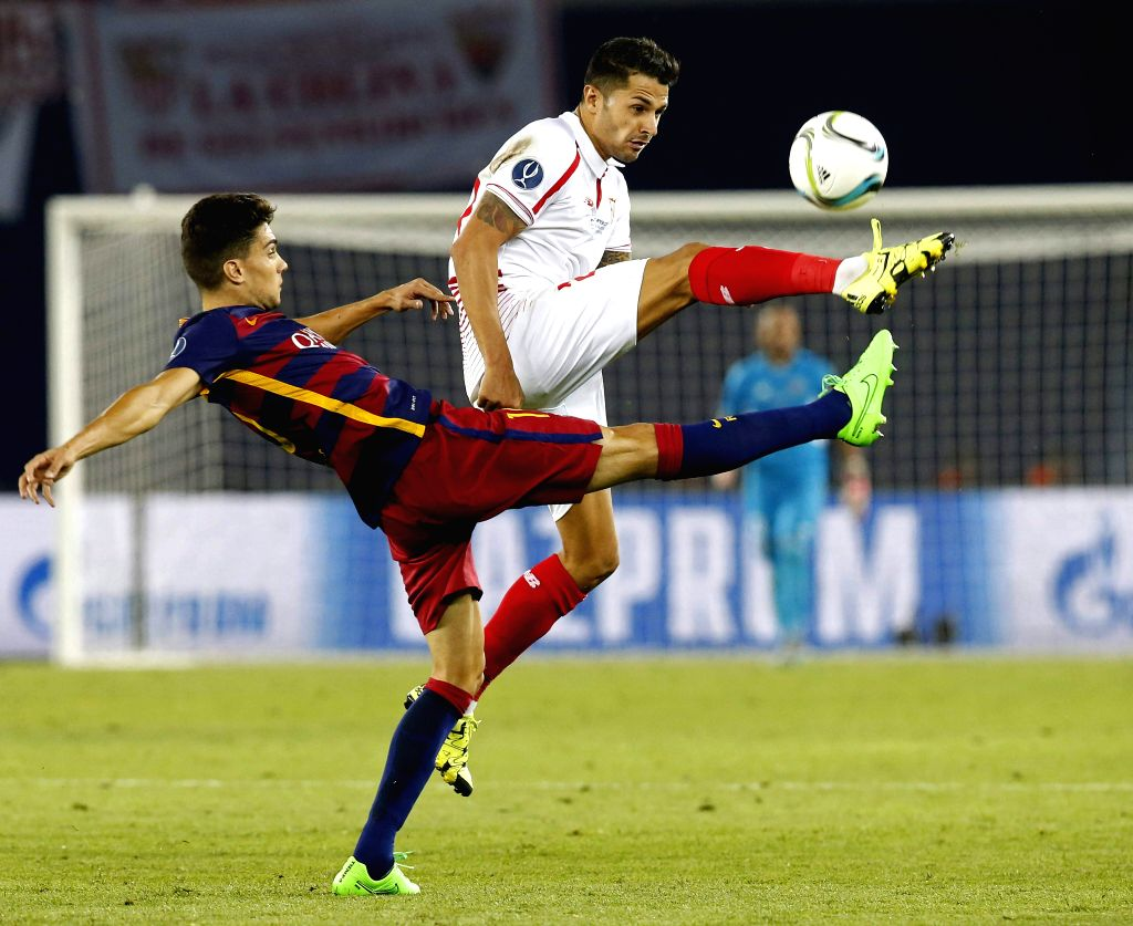 Barcelona's Marc Bartra (c) views for the ball against Vitolo (R) of Sevilla during the UEFA Super Cup match between Barcelona and Sevilla at Boris Paichadze Dinamo Arena in Tbilisi, ...
