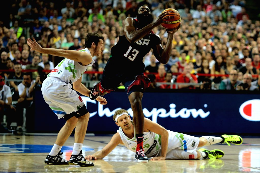 James Harden (C) of the United States drives the ball in front of Goran Dragic (L) of Slovenia during a quarterfinal of the 2014 FIBA Basketball World Cup Spain .