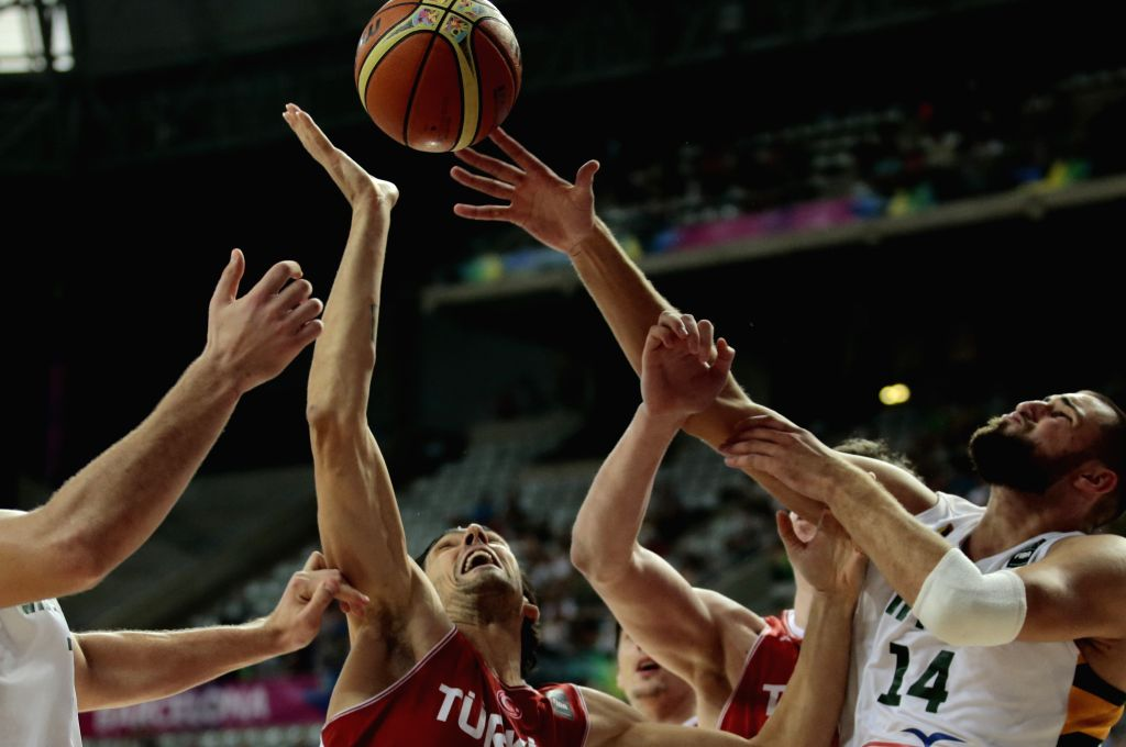 Kerem Gonlum (C) of Turkey vies with Jonas Valanciunas (R) of Lithuania during the quarterfinal match at the 2014 FIBA Basketball World Cup Spain, in Barcelona, .