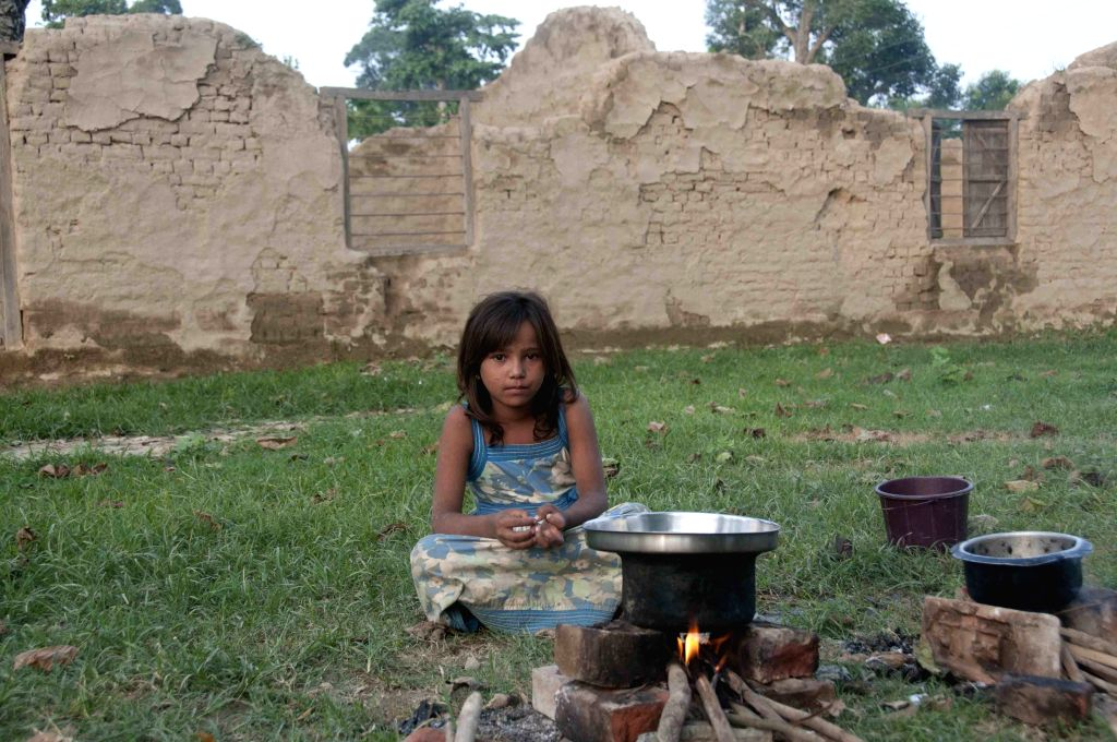 A girl cooks in front of her damaged house in flood in Bardiya, Nepal, Aug. 22, 2014. The death toll from floods in the northern Indian state of Uttar Pradesh over .