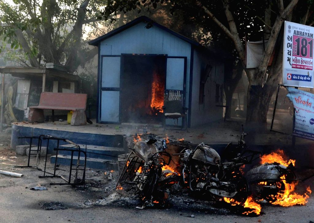 Baroda : A view of a building and vehicles that were torched after violence broke out during a Baroda Municipal Corporation demolition drive  on May 31, 2016.